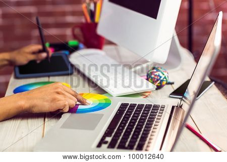 Graphic designer working with colour chart and digitizer at workplace