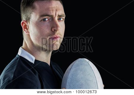 Side view of a rugby player holding a rugby ball