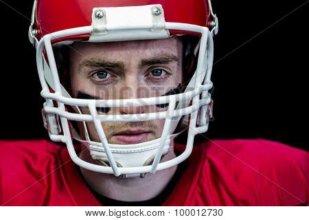 Portrait of focused american football player wearing his helmet against black background