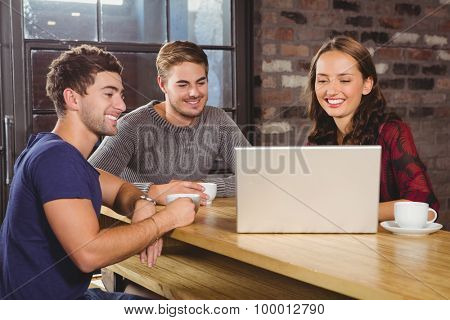Smiling friends having coffee together and looking at laptop at coffee shop