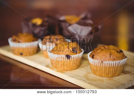 Chocolate chip muffins on cutting board at coffee shop
