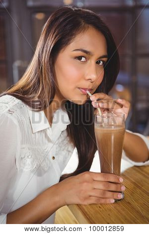Portrait of a beautiful woman drinking a hot chocolate in a cafe