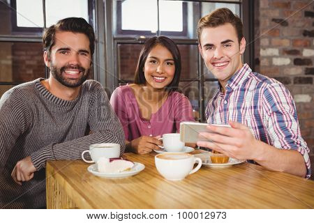 Group of friends looking at a smartphone in a cafe