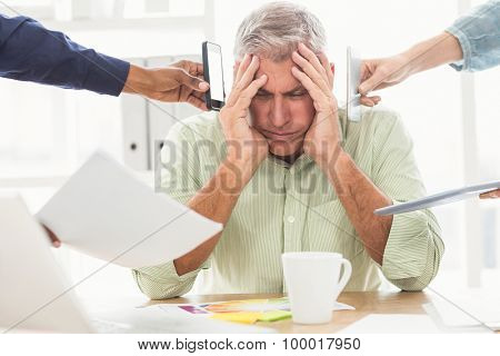 Overwrought businessman with hands on head at the office