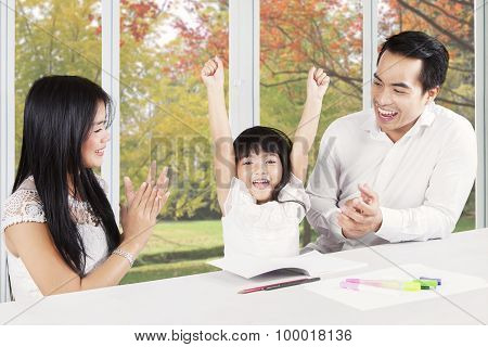 Happy Parents Applauding On Their Daughter