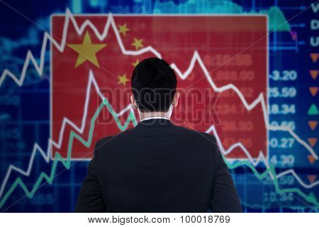 Man Looking At A Declining Graph With Chinese Flag