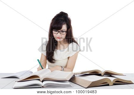 Student Doing School Task While Writing On The Book