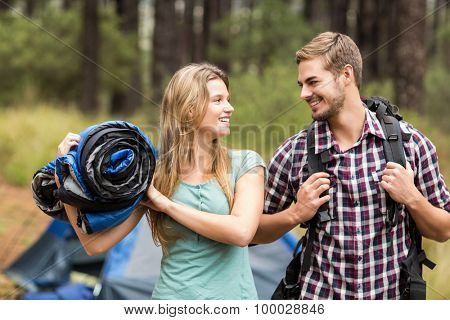 Young pretty hiker couple holding a sleeping bag and backpack in the nature