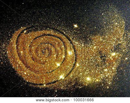 Blurry golden glitter sparkle on black background like a star galaxy