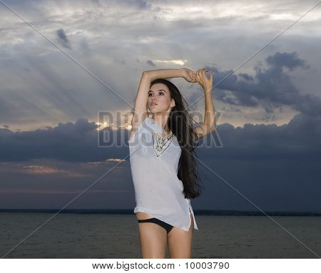 Sexy Brunette Woman Over Dusk Sky At Sunset