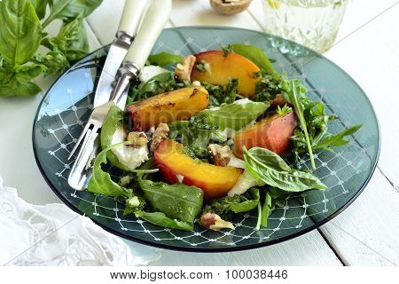 Salad with peaches, arugula, cream cheese, pesto and walnuts