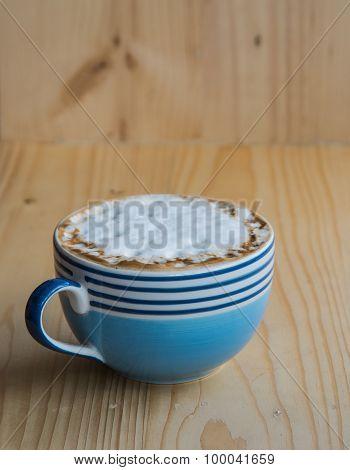 Latte In Blue Glass on wooden floor.
