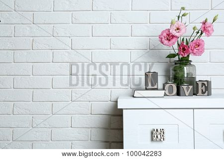 Beautiful flowers in vase with word Love on brick wall background