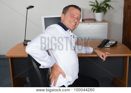 Businessman Suffering From Back Ache In Front Of Laptop In The Office