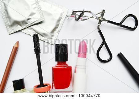 Couple of condoms and a cosmetics set with black mascara, pink and red nail polish and lipstick and