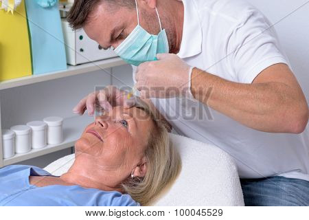 Male Clinician Injecting On Face Of A Woman