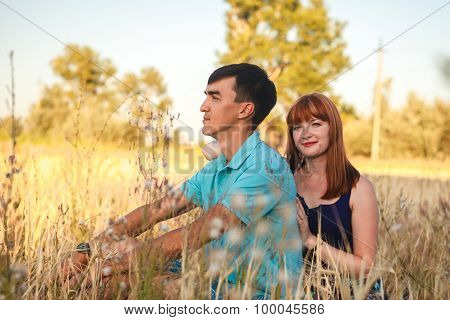 Young Couple Sitting Side By Side In The Field, Outdoors