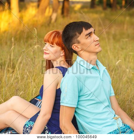 Beautiful Young Couple Sitting In The Field; Outdoors
