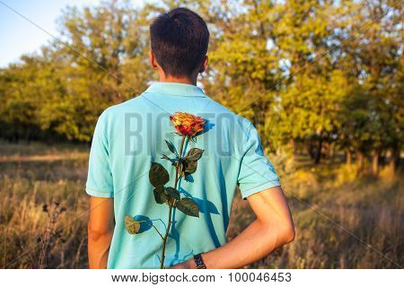 Man Holding A Rose Behind His Back In A Park Outdoors