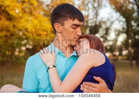 Girl Sitting On The Back Of A Guy Walk In The Park Outdoors