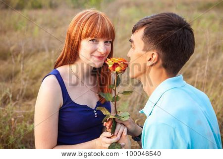 Young Couple In Love Looking At The Flower In The Park, Close-up