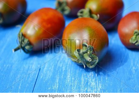 Big dark red tomatoes on bright blue background