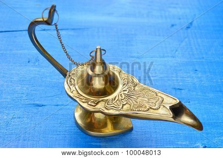 Magical genie lamp isolated on a blue wooden background