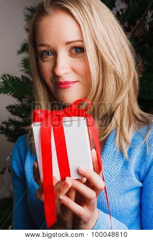Portrait of woman holding white gift