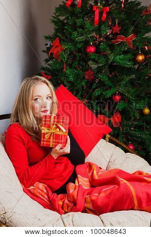 Nice woman sits in chair with present