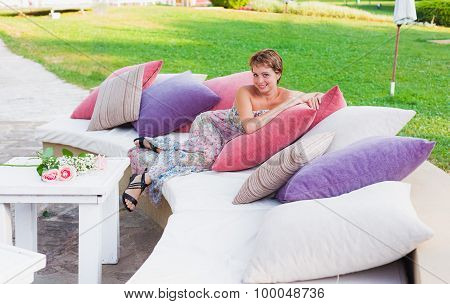 Lovely woman laying on sofa outdoors