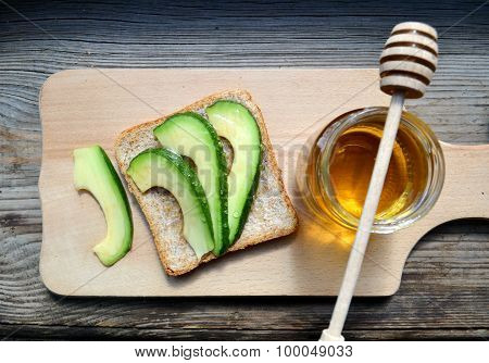 Golden honey with honeystick and a healthy sandwich with green avocado on wooden board