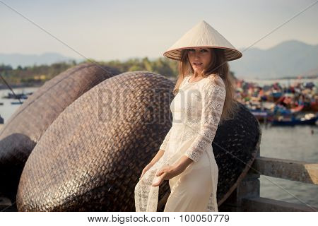 Blonde Girl In Vietnamese Dress Touches Hat By Barrier