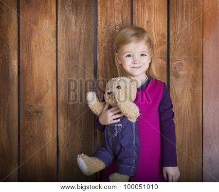 Portrait Of The Little Smiling Girl With Toy Bear