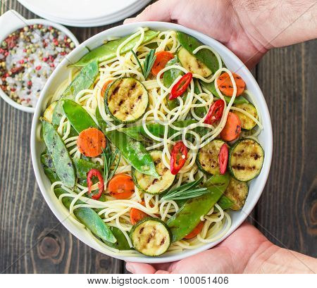 Spaghetti and grilled vegetables - zucchini, carrots, pea pods and rosemary