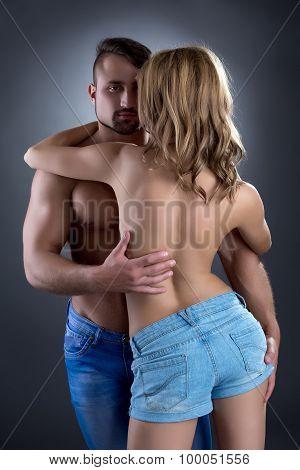 Handsome bodybuilder hugging slim topless girl