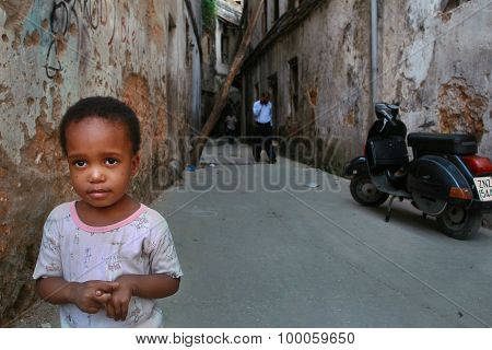 Little Child Standing In A Courtyard An Old Dilapidated House.