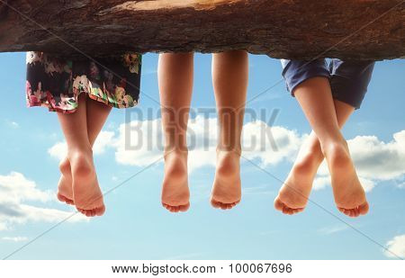 Three kids sitting in a tree dangling their feet against a blue sky in summer concept for family, friends, carefree and vacations