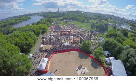 MOSCOW - JUN 06, 2015: Crowd of people walk by park during open air holiday Times and Epochs in Kolomenskoe district at summer sunny day. Aerial view