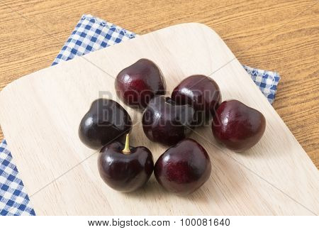 Group Of Red Plums On A Wooden Cutting Board