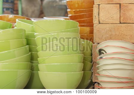 Stack of green and brown bowl in warehouse.