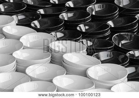 Stack Of Black And White Plates In Warehouse.