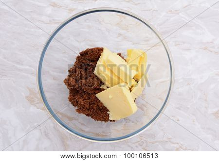 Pats Of Butter With Dark Soft Sugar In A Bowl