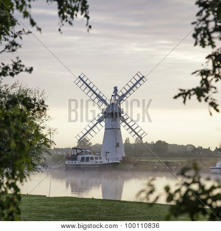 Stunning Landscape Of Windmill And River At Dawn On Summer Morning