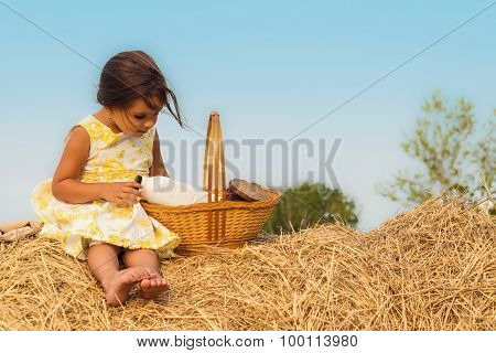 Little Girl Sitting On Haystack With A Basket Of Healthy Food