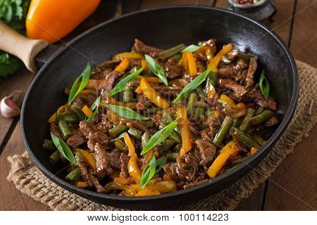 Stir frying beef with sweet peppers and green beans