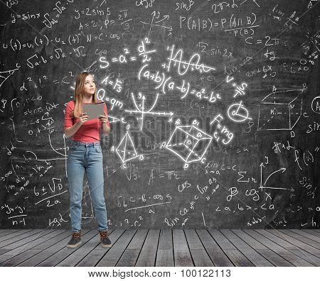 Young Lady Is Pondering About Complicated Math Problem. Formulas And Graphs Are Drawn On The Black C