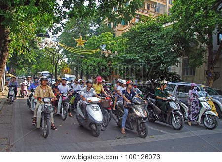 people on scooters are waiting green signal of traffic light