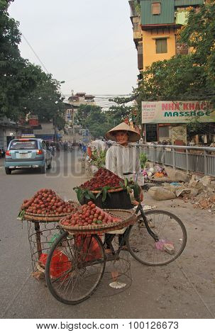 woman is selling litchi on the street in Hanoi, Vietnam