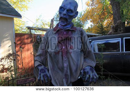 Creepy zombie monster in front of hearse