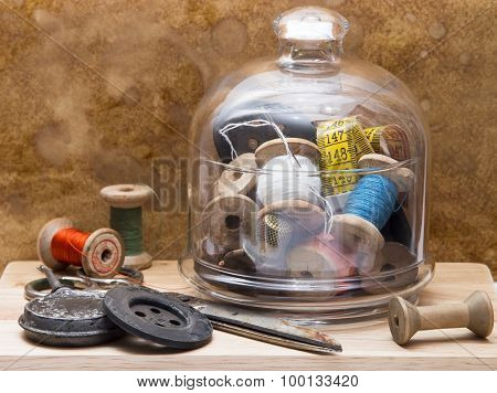 spools of colored thread and tools for sewing in a glass vase , buttons, oiler  and needles on the w